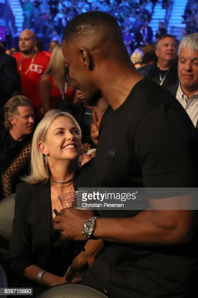 Actor Jamie Foxx speaks with actress Charlize Theron prior to the super welterweight boxing match between Floyd Mayweather Jr and Conor McGregor on...