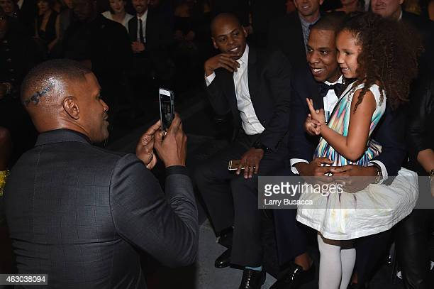 Actor Jamie Foxx takes a picture of his daughter Annalise Bishop with recording artist Jay Z during The 57th Annual GRAMMY Awards at the STAPLES...