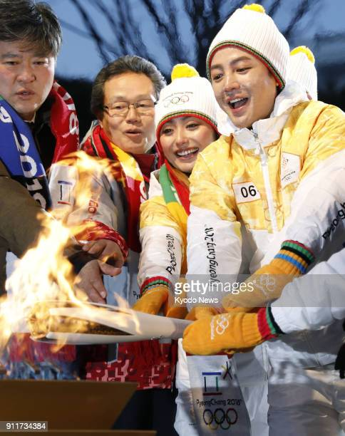 Actor Jang Keun Suk and former Olympic figure skater Miki Ando light a cauldron in Chuncheon South Korea on Jan 29 with the Olympic torch during the...