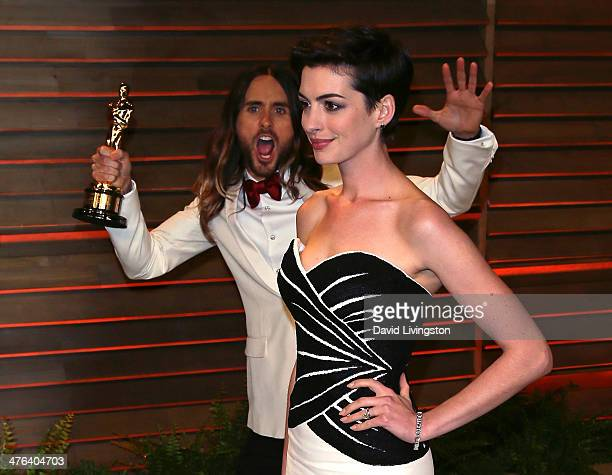 Actor Jared Leto photobombs actress Anne Hathaway at the 2014 Vanity Fair Oscar Party hosted by Graydon Carter on March 2, 2014 in West Hollywood,...