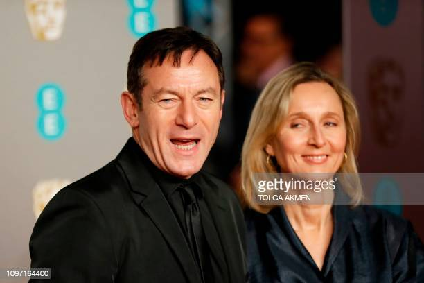 Actor Jason Isaacs and his wife Emma Hewitt pose on the red carpet upon arrival at the BAFTA British Academy Film Awards at the Royal Albert Hall in...