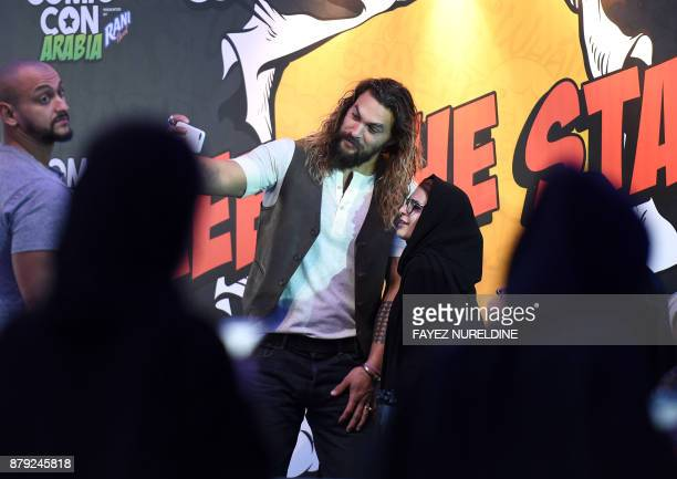 US actor Jason Momoa uses a cell phone to pose for a 'selfie' photograph with a Saudi woman as they attend the first ever ComicCon Arabia event held...