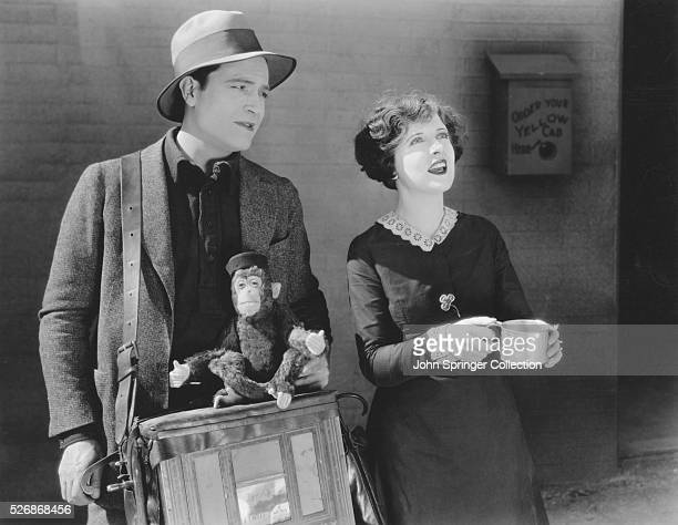 Actor Jason Robards Sr and actress May McAvoy play music on an organ and panhandle in a street in the 1927 film Irish Hearts Robards plays Rory and...