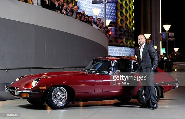 Actor Jason Statham appears next to a 1970 EType Series 2 Jaguar coupe as he arrives at a screening of CBS Films' 'The Mechanic' at the Planet...