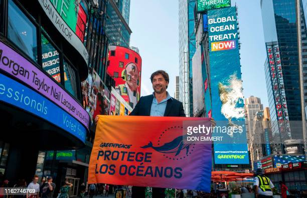 TOPSHOT Actor Javier Bardem holds a banner for Greenpeace as he poses for photos in Times Square on August 19 2019 in New York Bardem is to address...