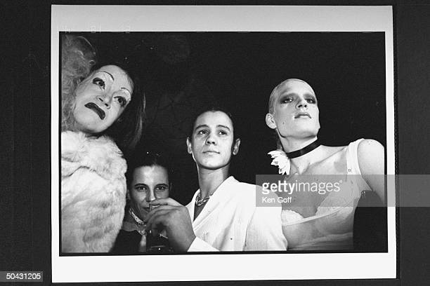 Actor Jaye Davidson clad in white suit holding drink as he poses w several drag queens at Fur is a Drag Party at the Heaven club