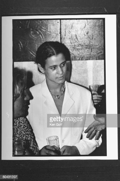 Actor Jaye Davidson clad in white suit holding drink while listening to several patrons during Fur is a Drag Party at the Heaven club