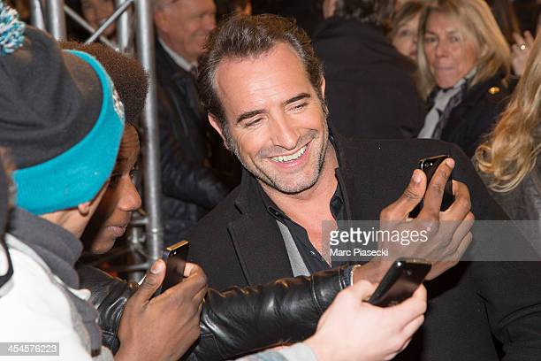Actor Jean Dujardin poses with fans as he attends the 'The Wolf of Wall Street' Paris Premiere at Cinema Gaumont Opera on December 9 2013 in Paris...