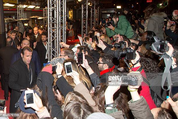 Actor Jean Dujardin signs autographs as he attends the 'The Wolf of Wall Street' Paris Premiere at Cinema Gaumont Opera on December 9 2013 in Paris...