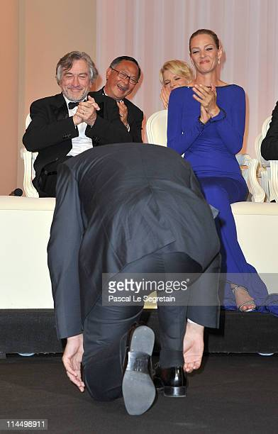 Actor Jean Durjardin kneels in front of Jury President Robert De Niro and jury member Uma Thurman on stage after winning the Best Actor Award for The...