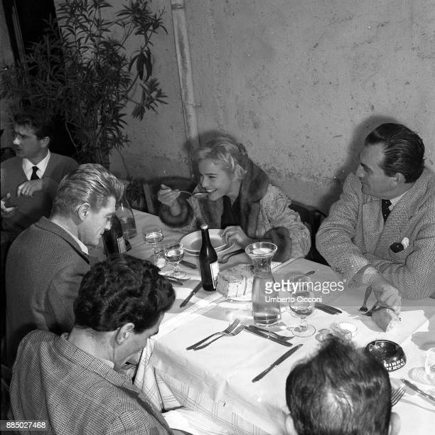 Actor Jean Marais actress Maria Schell director Luchino Visconti and other people during a lunch break while shooting the movie 'Le notti Bianche'...