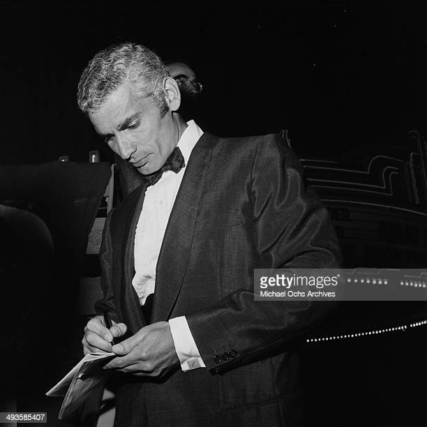 Actor Jeff Chandler signs autographs at the movie premiere party of Trapeze in Los Angeles California