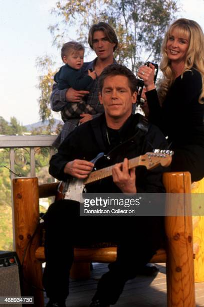 Actor Jeff Conaway poses for a portrait with his family including Rona NewtonJohn as he plays guitar at home in circa 1991 in Los Angeles California