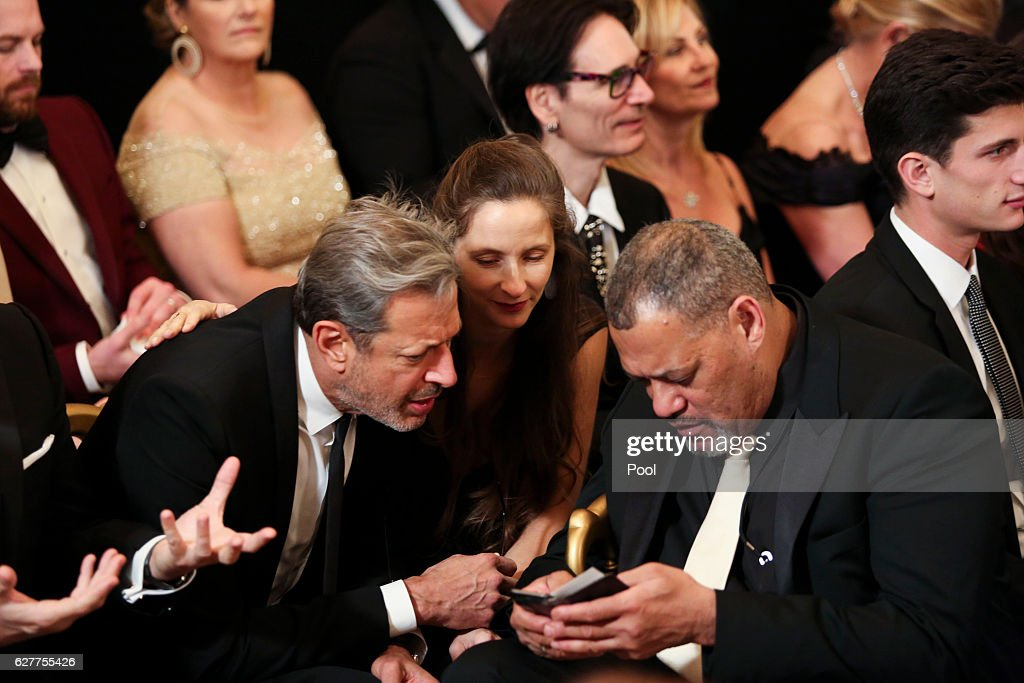 Actor Jeff Goldblum (L), his wife Emily Goldblum and actor Laurence Fishburne attend a ceremony for the 2016 Kennedy Center honorees December 4, 2016 in the East Room of the White House in Washington, DC. The honorees include Eagles band members, actor Al Pacino, singer James Taylor, pianist Martha Argerich and singer Mavis Staples.