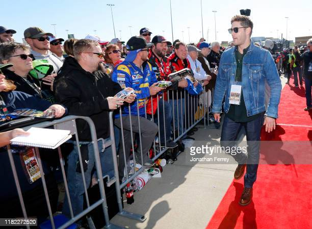 Actor Jensen Ackles signs autographs on the red carpet for the driver's meeting before the Monster Energy NASCAR Cup Series Hollywood Casino 400 at...