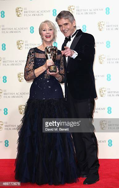 Actor Jeremy Irons poses with actress Dame Helen Mirren after presenting her with her Bafta Fellowship award in the winners room at the EE British...