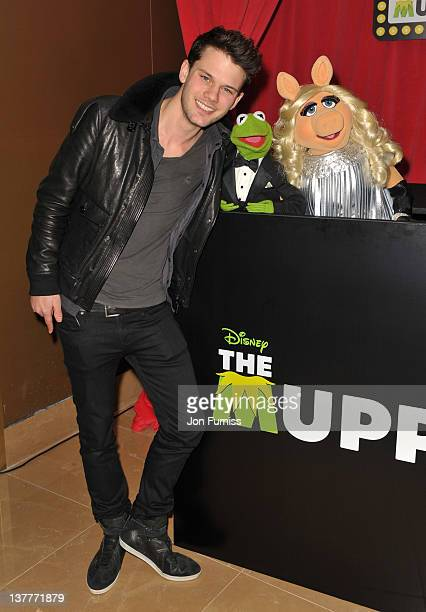 Actor Jeremy Irvine poses with Kermit and Miss Piggy at the UK premiere of 'The Muppets' at The Mayfair Hotel on January 26 2012 in London England