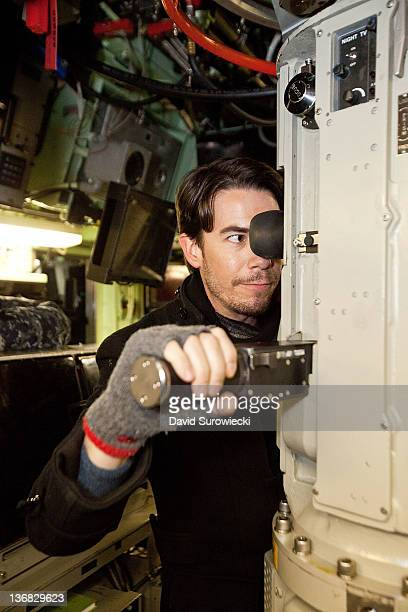 Actor Jerry Trainor uses the periscope onboard the submarine USS Hartford at Naval Submarine Base New London on January 11 2012 in Groton Connecticut...