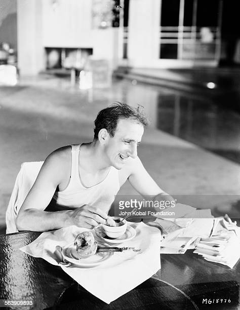 Actor Jimmy Durante reading from a stack of letters while he eats breakfast for MGM Studios 1931