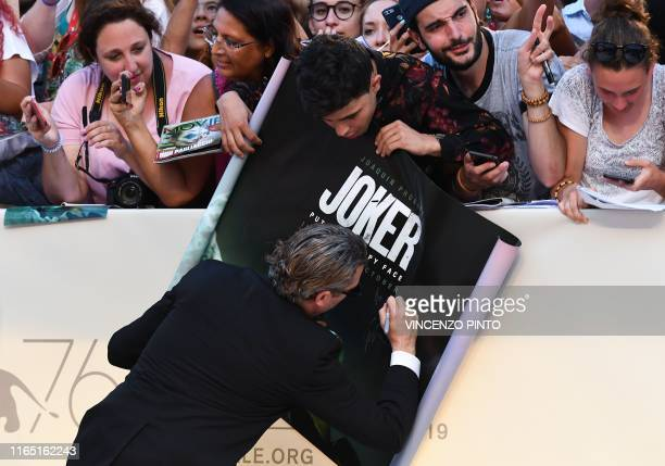 US actor Joaquin Phoenix signs the movie's poster for a fan as he arrives for the screening of the film Joker on August 31 2019 presented in...