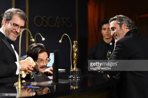 TOPSHOT US actor Joaquin Phoenix waits as his award for Best Actor in a Leading Role for Joker is engraved as he attends the 92nd Oscars Governors...
