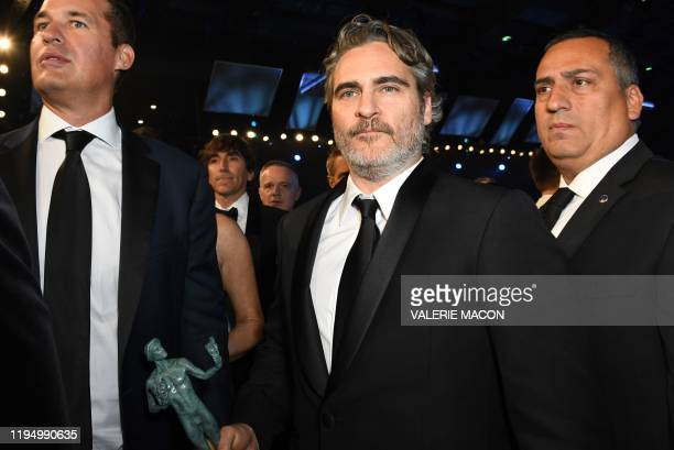 US actor Joaquin Phoenix walks with his trophy for Outstanding Performance by a Male Actor in a Leading Role during the 26th Annual Screen Actors...