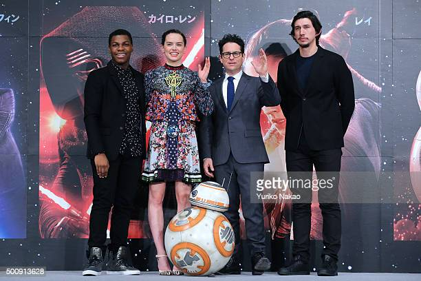 Actor John Boyega actress Daisy Ridley director JJ Abrams and actor Adam Driver pose with BB8 at the press conference for 'Star Wars The Force...