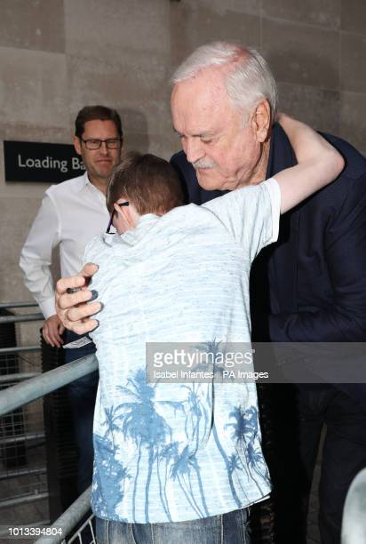 Actor John Cleese hugs a young fan outside BBC Broadcasting House in London after appearing on The One Show with his daughter Camilla Cleese