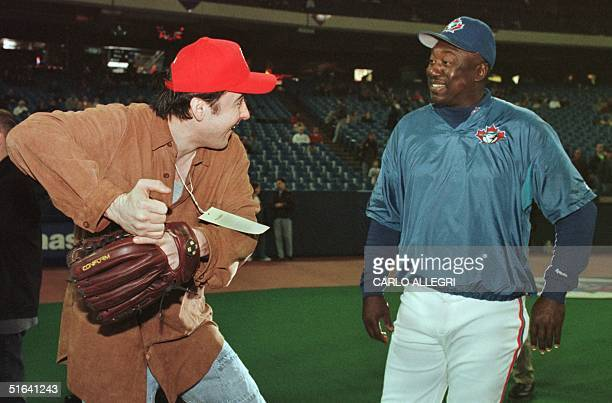 Actor John Cusack shows Toronto Blue Jay hitting coach Gary Matthews his style during batting practice before a spring training game against the St...
