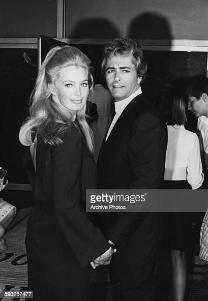 Actor John Derek and his wife Linda Evans holding hands at the Emmy Awards May 1968