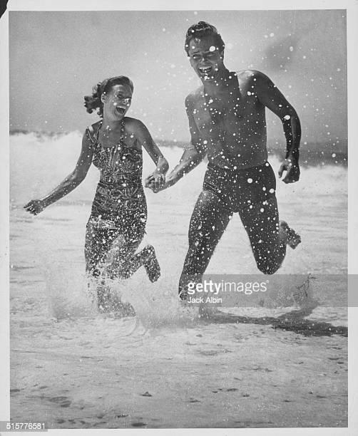Actor John Derek and his wife Pati Behrs running through the surf on a beach, at Seafair, Laguna Beach, California, circa 1955.