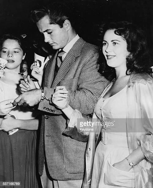 Actor John Derek signing autographs for fans as fan Mickey Mosko handcuffs herself to the star Philadelphia circa 1951