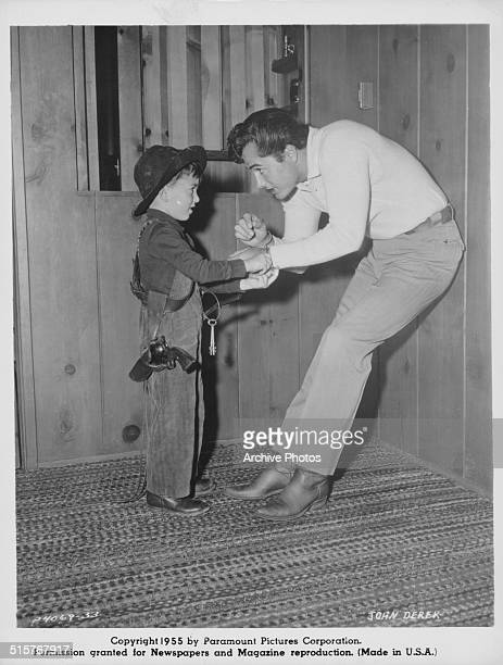 Actor John Derek with a little boy in cowboy costume on the set of the movie 'Run for Cover' 1955