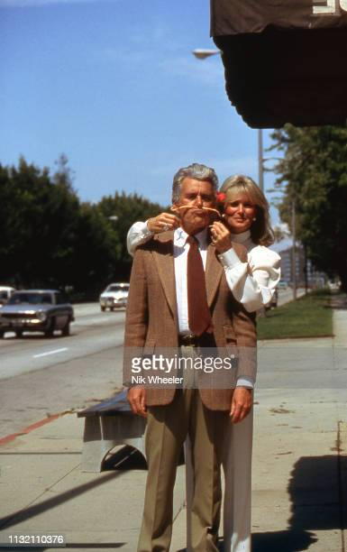 """Actor John Forsyth and actress Linda Evans, stars of soap opera """"Dynasty"""" joke together on street outside film studio in Hollywood, Los Angeles,..."""