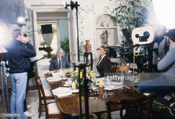 "Actor John Forsythe and actress Linda Evans with film crew on the set of television soap opera ""Dynasty"" during filming opf the television series..."