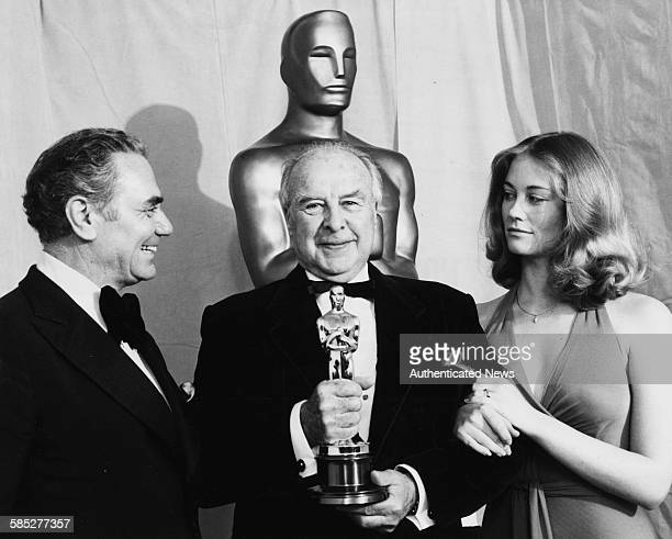 Actor John Houseman holding his Best Supporting Actor Oscar for the film 'The Paper Chase' with presenters Ernest Borgnine and Cybill Shepherd at the...