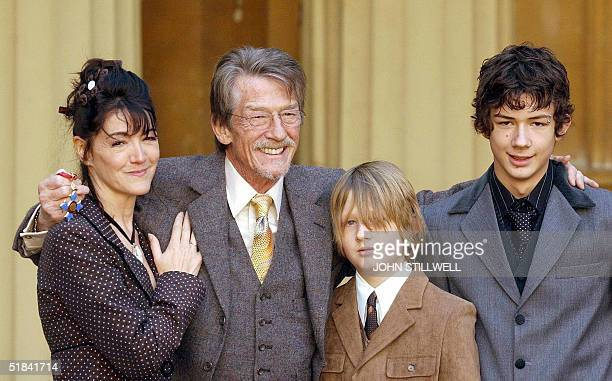 Actor John Hurt laughs as he holds his CBE with fiancee Anwen ReesMyers and sons Nicholas aged 11 and Alexander aged 14 after it was presented to him...
