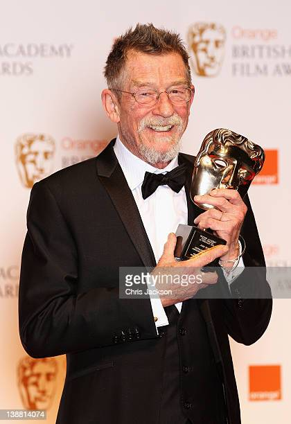 Actor John Hurt poses in the press room with the Oustanding British Contribution award during the Orange British Academy Film Awards 2012 at the...