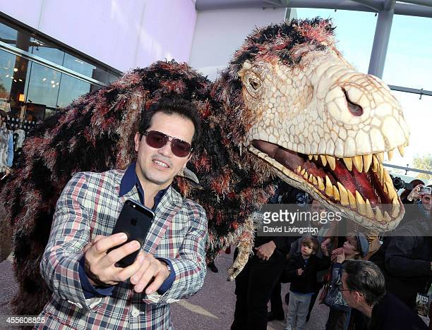 Actor John Leguizamo shoots a selfie with a dinosaur puppet at the 'Walking with Dinosaurs' press event at the Natural History Museum on December 12...
