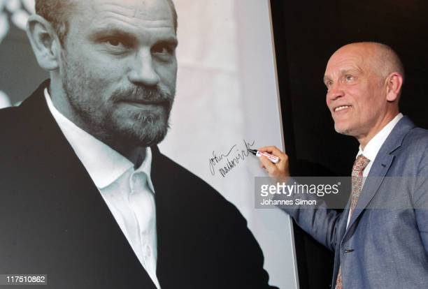 US actor John Malkovich signs his photographic portrait after the CineMerit award ceremony during the Muenchen Filmfest on June 27 2011 in Munich...