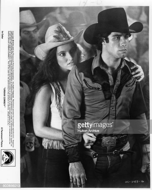 Actor John Travolta and actress Madolyn Smith Osborne look on in a scene during the Paramount Pictures movie 'Urban Cowboy circa 1980