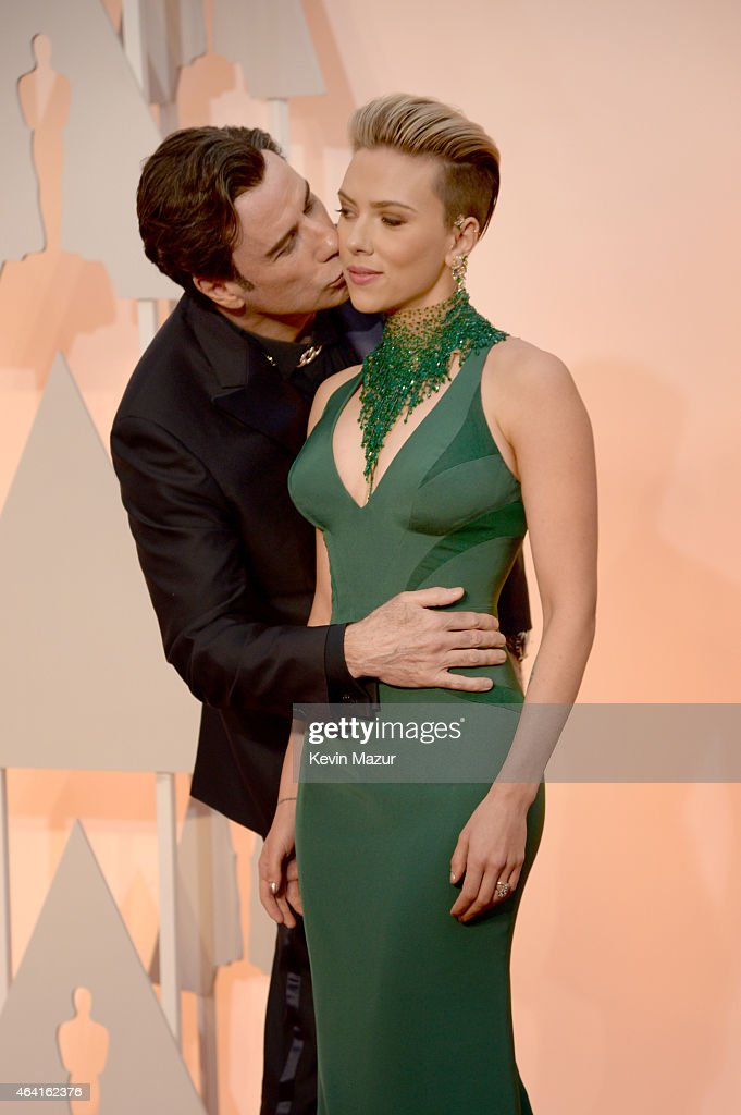 Actor John Travolta (L) and actress Scarlett Johansson attend the 87th Annual Academy Awards at Hollywood & Highland Center on February 22, 2015 in Hollywood, California.