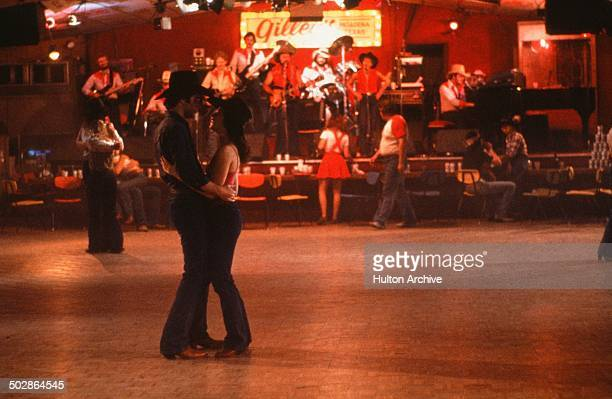 Actor John Travolta and Debra Winger dance at Gilley's in a scene during the Paramount Pictures movie 'Urban Cowboy circa 1980
