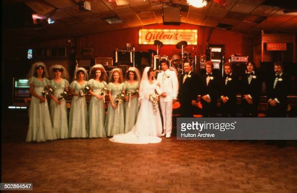 Actor John Travolta and Debra Winger pose for a wedding picture at Gilley's in a scene during the Paramount Pictures movie 'Urban Cowboy' circa 1980