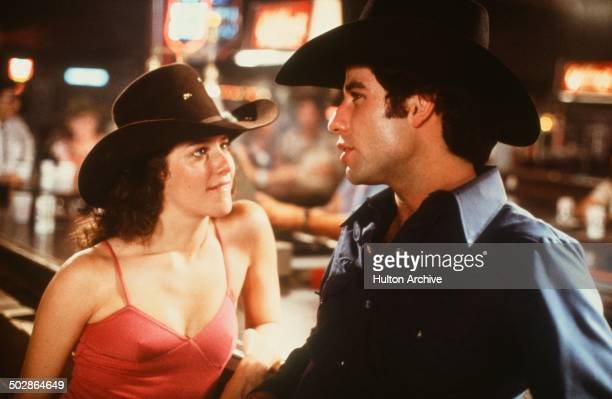 Actor John Travolta and Debra Winger talk in a scene during the Paramount Pictures movie 'Urban Cowboy' circa 1980
