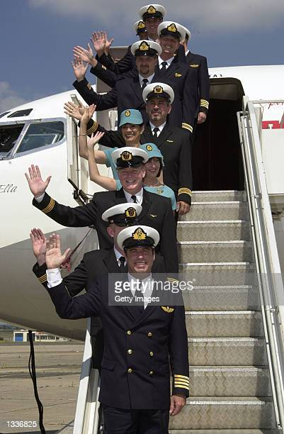 Actor John Travolta and fellow pilots and attendants who recently completed a training course with airline Qantas pose in front of Travolta?s vintage...
