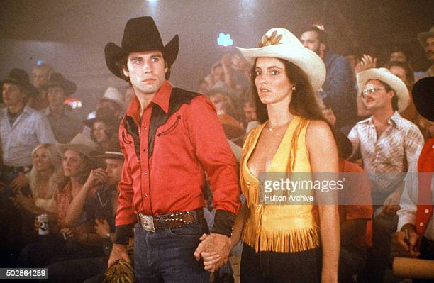 Actor John Travolta and Madolyn Smith Osborne walk in a scene of the Paramount Pictures movie 'Urban Cowboy' circa 1980