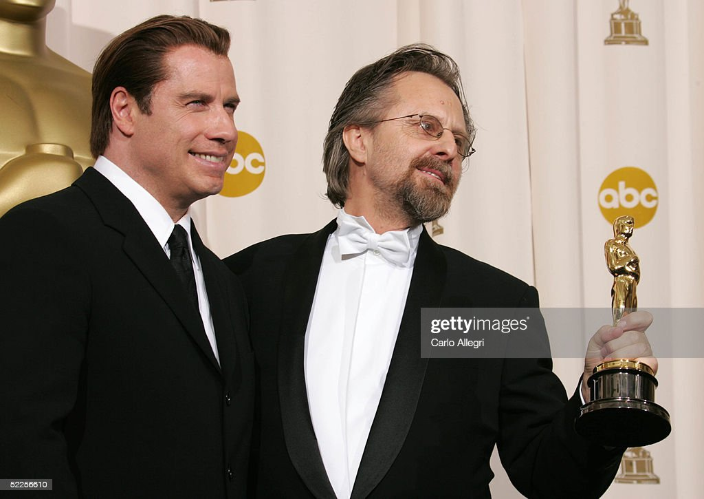 Actor John Travolta and musician Jan A.P. Kaczmarek, winner of Achievement in music written for motion pictures (Original score) for 'Finding Neverland' pose backstage during the 77th Annual Academy Awards on February 27, 2005 at the Kodak Theater in Hollywood, California.