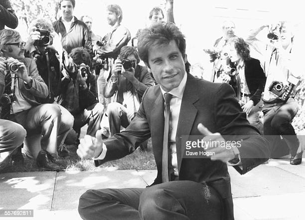Actor John Travolta giving the thumbs up, surrounded by photographers as he adds his hand and foot prints to the cement at Grauman's Chinese Theatre,...