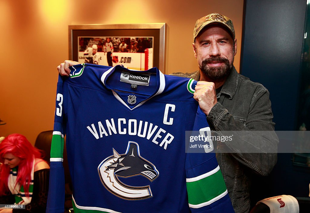 Actor John Travolta holds a Vancouver Canucks jersey during the NHL game between the Vancouver Canucks and the Tampa Bay Lightning at Rogers Arena October 18, 2014 in Vancouver, British Columbia, Canada.